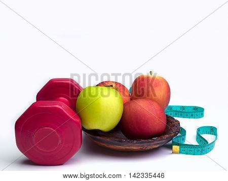 Red dumbbells weight with measuring tape and apple for diet concept on white background
