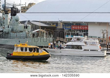 SYDNEY, AUSTRALIA - APRIL, 2016 : Yellow Water taxi passing yacht, Destroyer HMAS Vampire ship in front of Australian National Maritime Museum, Darling Harbour in Sydney, Australia on April 19, 2016