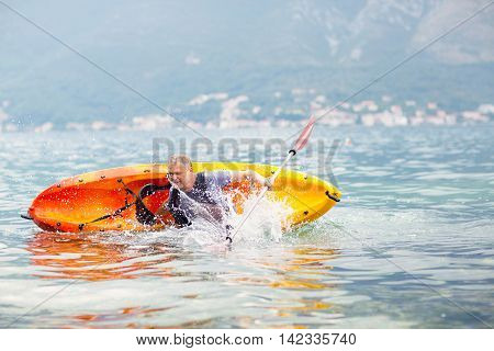 Mature man kayaking on the sea falling out of the kayak