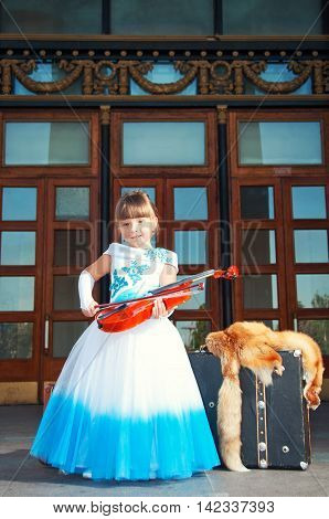 Retro style. Musician violinist. Girl in a magnificent dress near old suitcases violin fox fur