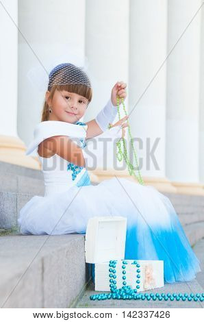 Little fashion-girl in magnificent blue and white evening dress sitting on the steps near the colonnade