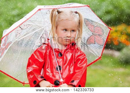 Serious Pensive Pretty Little Girl In Red Raincoat With Umbrella