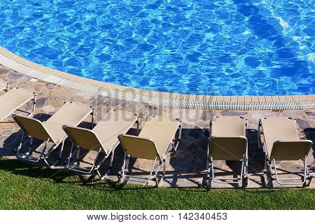 A row of sunbeds near a swimming pool