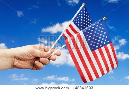 American flags in hand against the blue sky. freedom