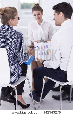 Shot of smiling employees talking about results at a business meeting