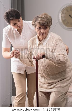 Elderly Woman With Staff And Helpful Caregiver