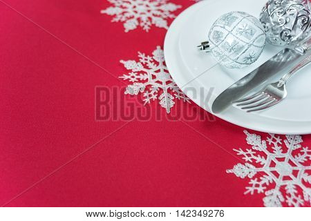 Christmas table: silver knife and fork beautiful Christmas ball are on the white porcelain plate which is located on a table covered with a red tablecloth; with space for text