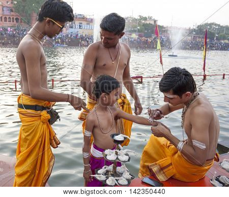 Ujjain Madhya Pradesh India - May 18 2016: A young priest paints the arm of a boy-apprentice before a fire ceremony called 'aarti' at the Kshipra River during the Kumbh Mela religious festival in Ujjain India on May 18 2016. The Kumbh Mela is the largest