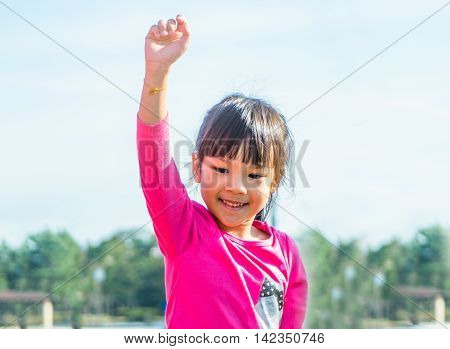 Asian Girl put her hand up high Winner in the sky