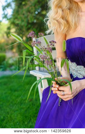 Blonde Beautiful woman in long purple dress sitting at garden table in green garden.