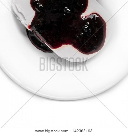 Ice cream with blueberry jam. Delicious cold dessert. Frozen sweet cream. Sweet food on the plate - ice cream and syrup.