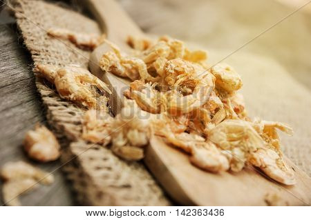 Dried shrimp on wooden spoon and texture background vintage style
