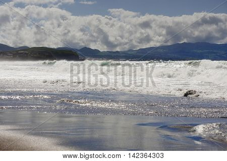 beautiful amazing beach of Ribeira Grande in Sao Miguel island in Azores Portugal with wild sea waves breaking on sand shore under early summer silver light in tourism and travel destination concept