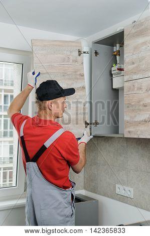 Installation of kitchen. Workman installs doors to kitchen cabinet.
