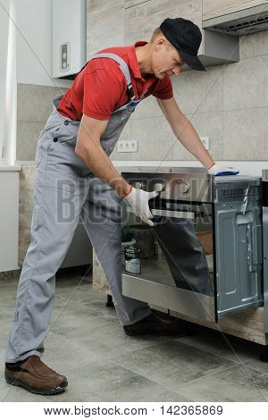 Installation of household appliances. Workman installing a built-in electric oven.