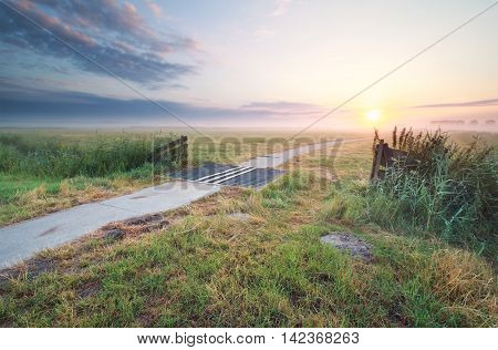 beautiful summer sunrise on farmland over biking path