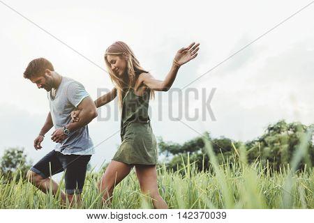 Young Couple Walking Through Meadow