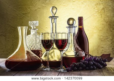 Decanters with red wine and glass on stucco background wiht clipping path.
