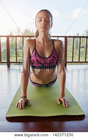 Shot of fitness woman doing core stretch workout on yoga mat. Healthy young female doing cobra pose on exercise mat at yoga class.