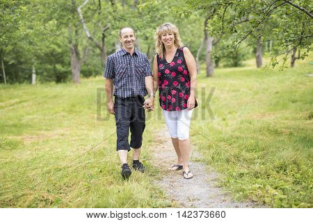A Happy fifty couple in park walking