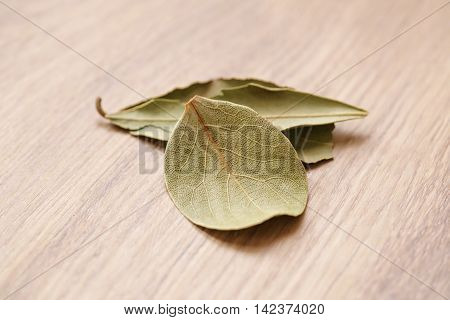 dried bay leaves on wood oak table, shallow focus