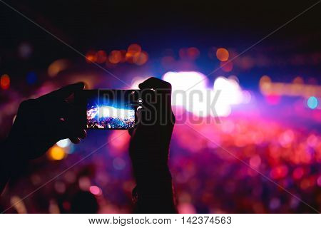 Silhouette Of Hands Using Camera Phone To Take Pictures And Videos At Music Concert, Festival. Soft