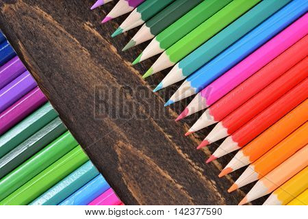 Mixed colored pencils tips on wenge wood table