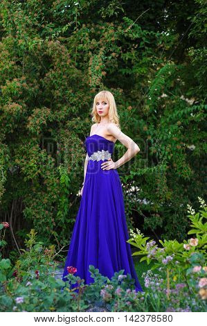 Portrait of beautiful woman dressed in evening gown. Blonde Beautiful woman in long purple dress like princess in green garden.