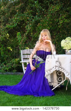 Portrait of beautiful woman dressed in evening gown. Blonde Beautiful woman in long purple dress like princess sitting at a garden table in green garden. Woman holding a bouquet of wildflowers