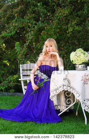 Beautiful woman dressed in evening gown. Blonde Beautiful woman in long purple dress like princess sitting at garden table in green garden. Woman holding bouquet of wildflowers. Look at camera.