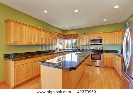 Spacious Kitchen With Green Walls And Hardwood Floor