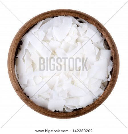 Coconut flakes in a bowl on white background, also called copra. Dried and grated flesh or meat of the coconut kernel. Edible, raw and organic food. Isolated close up macro photo from above.
