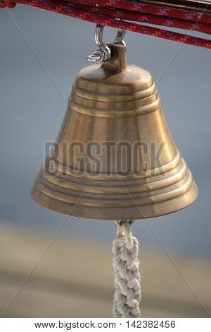 Bronze bell hanging on a yacht sunlit