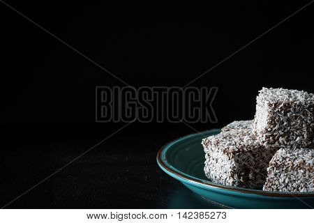 Chocolate Lamingtons on Dark Background with Copy Space