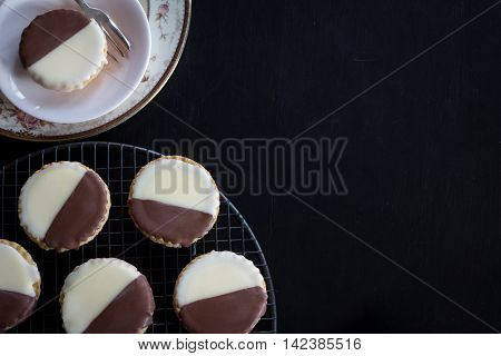 Neenish Tarts on Rack and Plate from Above on Dark Background with Copy Space