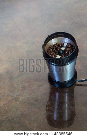 An electric coffee grinder with beans inside.