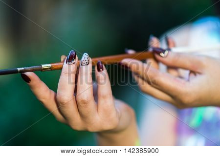 Beautiful hand of a young woman with brown manicure mouthpiece with cigarette
