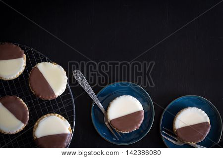 Neenish Tarts on Rack and Plate on Dark Background with Copy Space Horizontal from Above