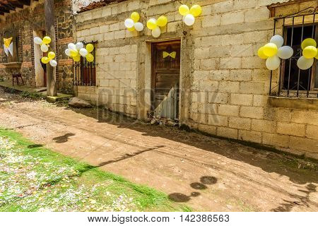 San Juan del Obispo Guatemala - June 24 2016: Houses adorned with balloons & pine needle carpets in street for St John's Day procession in village named after the patron saint. Near Antigua, UNESCO World Heritage Site.