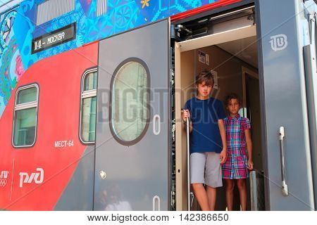 SOCHI, RUSSIA - AUG, 4, 2014: Brother and sister (models with releases) stand in High speed two-storied train and look outside.