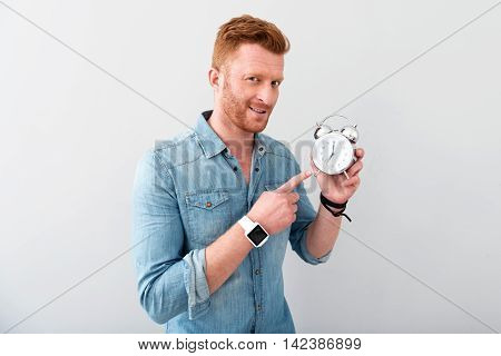 Mind the time. Positive bearded man holding alarm clock and expressing gladness while standing isolated on grey background
