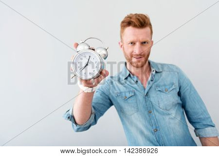 Save time. Close up of alarm clock n hands of pleasant delighted man holding it while standing isolated on grey background