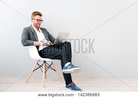 Business matters. Cheerful handsome man sitting in the chair isolated on grey background while using laptop