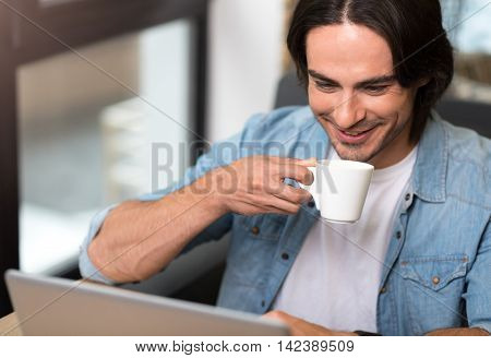 Charge your mind. Positive delighted man using laptop and smiling while drinking coffee