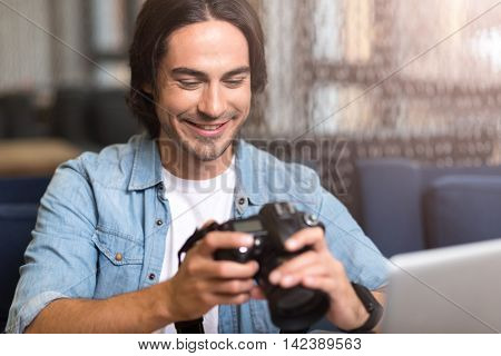 Real photographer. Cheerful delighted man sitting at the table and smiling while holding photo camera