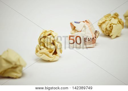 Crumpled euro bill among office paper. Business concept.