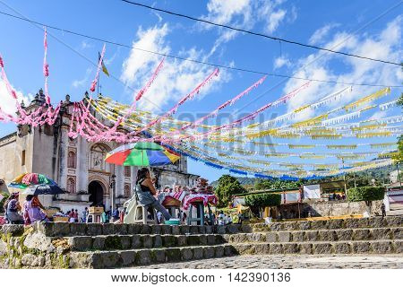San Juan del Obispo Guatemala - June 26 2016: Women sell food & villagers wait for procession to leave church as part of St John's Day celebrations in small village named after the patron saint. Near Antigua, a UNESCO World Heritage Site.