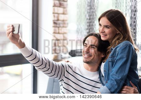 Say cheese. Joyful delighted couple smiling and making selfies while while resting in the cafe