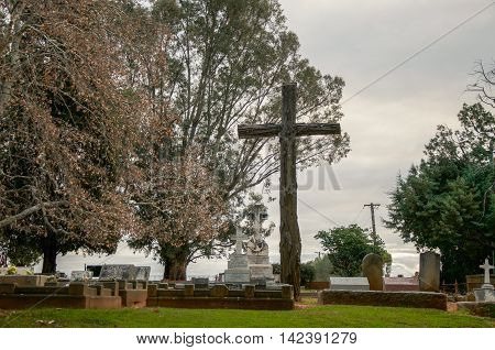 HENLEY BROOK,WA,AUSTRALIA-JULY 15,2016: Old cemetery with headstones and large rustic wooden cross at All Saints Church treed grounds at dusk in Henley Brook, Western Australia.
