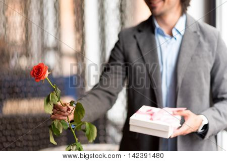 For you my dear. Close up of rose in hand of pleasant cheerful man holding it and giving present while expressing joy